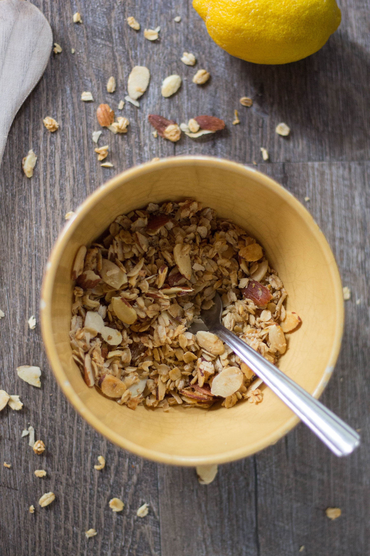 Vegan granola in yellow bowl with lemon in background.