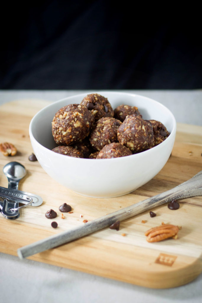 Vegan turtle bites in a white bowl with pecans and chocolate chips.
