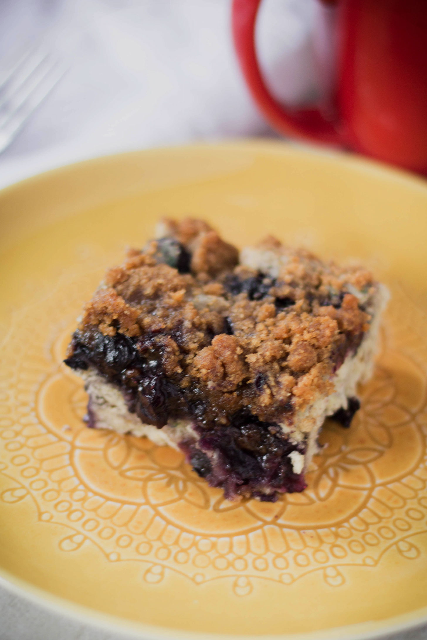 Close up of a piece of vegan blueberry coffee cake on a yellow plate with a red coffee cup in the background.