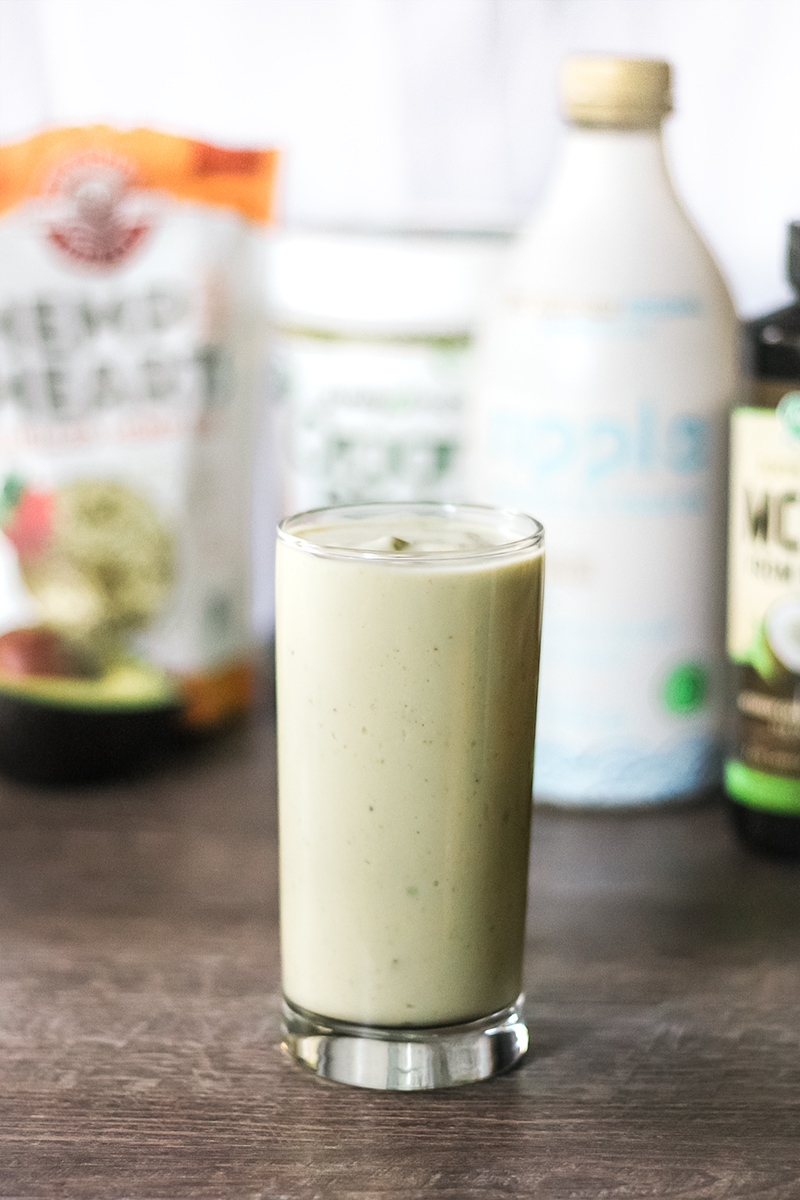 Vegan keto smoothie in a glass with the ingredients in the background.