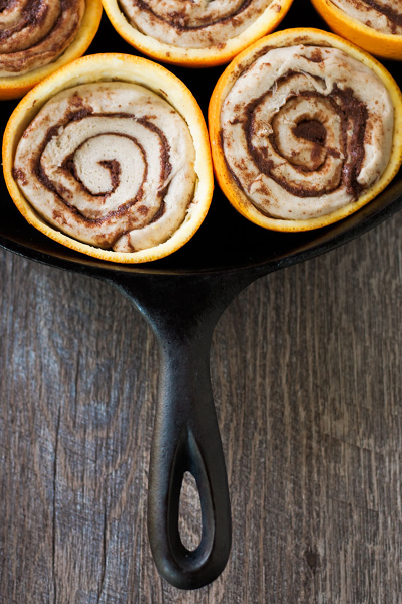 Uncooked cinnamon rolls in orange peels.