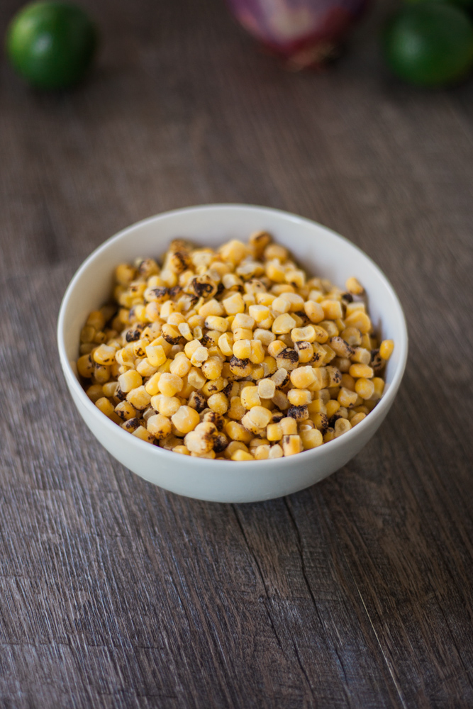 Frozen roasted corn in a white bowl.