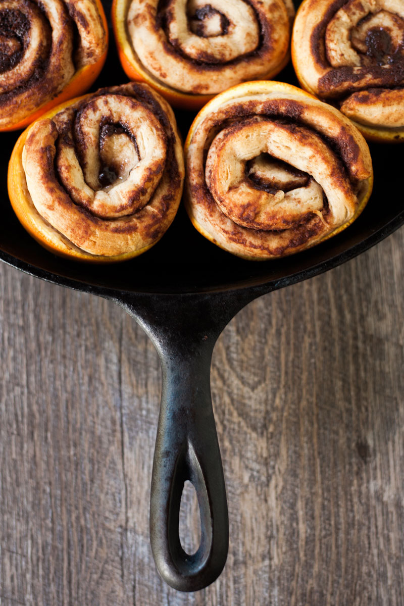 Baked cinnamon rolls in orange peels in a cast iron pan.