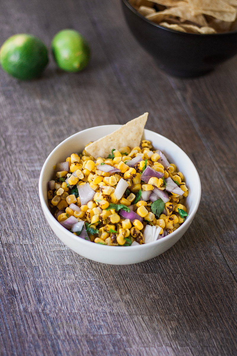 Corn salsa with a tortilla chip sticking out of it.