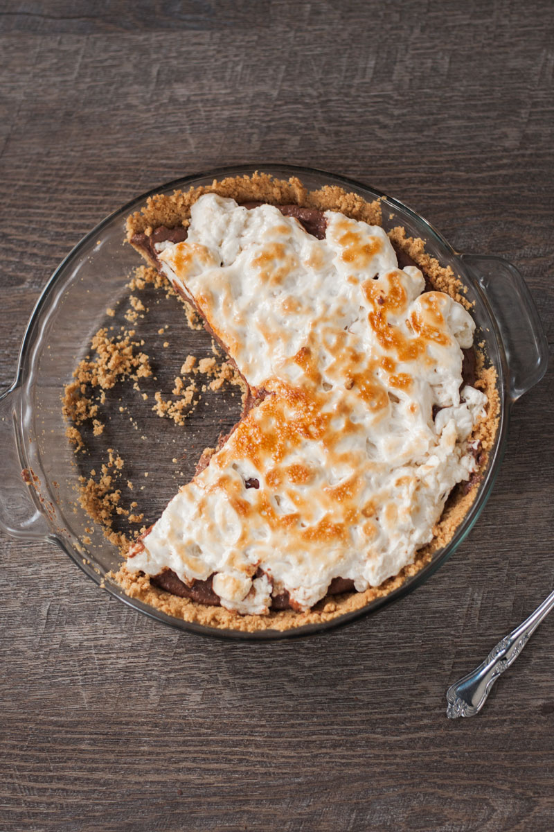 Vegan s'mores pie with a couple of slices missing on a wood background.
