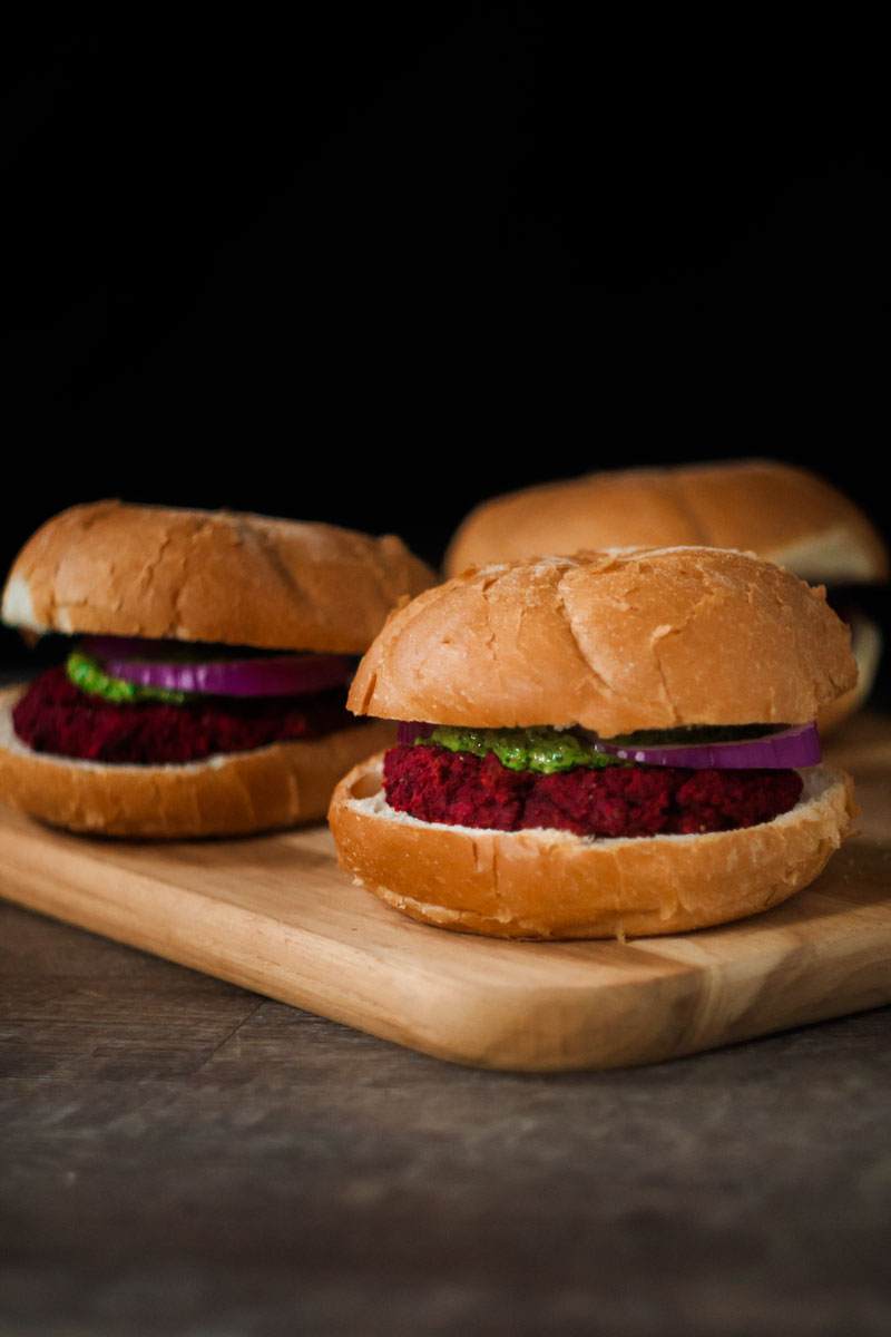 Vegan beet burgers on a cutting board.