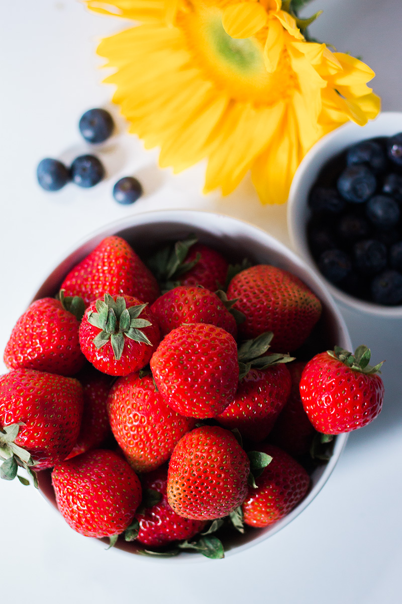 A large bowl of bright red strawberries and a smaller bowl of blueberries.